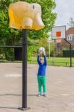 La ragazza che tende la palla al canestro gradisce l'elefante Fotografia Stock