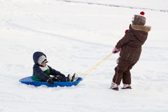 La ragazza che tira i bambini del ragazzo scherza la neve della slitta del toboggan  Immagini Stock