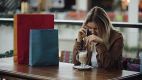 La ragazza chiama un numero sul telefono che si siede nel caffè con i sacchetti della spesa sulla tavola stock footage