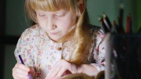 La ragazza cinque anni disegna la sera Accanto al suo vaso con le matite colorate archivi video