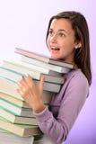La ragazza colpita dello studente porta la pila di libri Immagini Stock Libere da Diritti