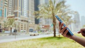 La ragazza compone un numero o un messaggio sullo smartphone contro il contesto delle vie della città del Dubai Passa il primo pi stock footage
