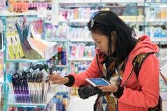 La ragazza compra i cosmetici nel deposito immagini stock libere da diritti