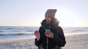 La ragazza comunica su Internet tramite il telefono e la mano d'ondeggiamento ciao stock footage