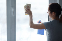 La ragazza con attenzione lava e pulisce una finestra Immagine Stock Libera da Diritti