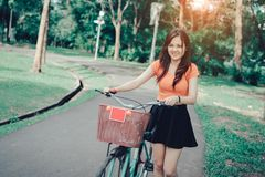 La ragazza con la bicicletta si rilassa e riposa il sorriso fotografia stock libera da diritti