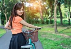La ragazza con la bicicletta si rilassa e riposa il sorriso fotografie stock