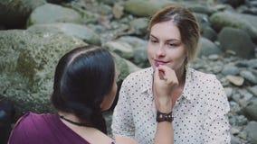 La ragazza con capelli intrecciati neri dipinge le labbra il suo amico con capelli biondi con la matita, trucco prima della fucil archivi video