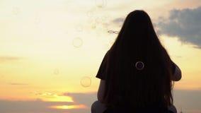 La ragazza con capelli lunghi inizia sulle bolle su un tetto della costruzione contro lo sfondo di un declino Gli inizio adorabil archivi video
