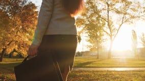 La ragazza con capelli lunghi sta camminando in parco nei raggi del tramonto e sta parlando sul telefono Natiche della donna in g video d archivio