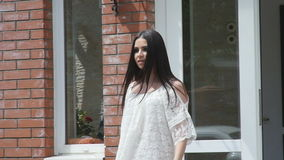 La ragazza con capelli lunghi in un bello vestito esce dalla casa stock footage