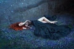 La ragazza con capelli rossi che si trovano sull'erba in foresta scura, regina nera ha perso nella battaglia, incantante signora  immagini stock
