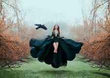 La ragazza con capelli rossi luminosi levita sopra terra, strega potente, dea della foresta in vestito volante nero con pizzo sop immagine stock