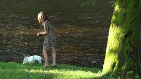 La ragazza con due animali domestici dei cani ha una passeggiata vicino al fiume nell'estate Colpo statico archivi video