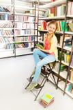La ragazza con due trecce e compresse si siede sulla scala Fotografia Stock Libera da Diritti