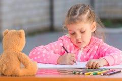 La ragazza con entusiasmo disegna con i pastelli nell'album immagine stock libera da diritti