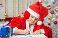 La ragazza con entusiasmo redige la cartolina di Natale di congratulazioni Immagine Stock
