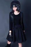 La ragazza con i capelli di scarsità scuri indossa i vestiti del motociclista bomber e casco Immagini Stock