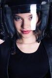 La ragazza con i capelli di scarsità scuri indossa i vestiti del motociclista bomber e casco Immagine Stock
