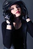 La ragazza con i capelli di scarsità scuri indossa i vestiti del motociclista bomber e casco Fotografia Stock