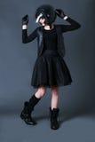 La ragazza con i capelli di scarsità scuri indossa i vestiti del motociclista bomber e casco Fotografie Stock