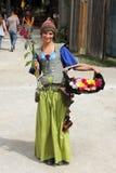 La ragazza con i fiori si è vestita in costume medioevale Fotografia Stock