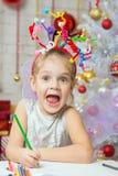 La ragazza con i fuochi d'artificio di un giocattolo sulla testa estrae una carta di congratulazioni dei nuovi anni Immagine Stock