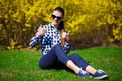 La ragazza con i pollici su si rilassa in parco su erba verde fresca vicino all'albero in fiore giallo Immagini Stock
