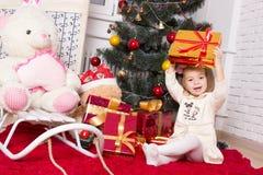 La ragazza con i regali sotto l'abete Fotografia Stock