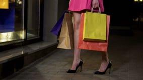 La ragazza con i sacchetti della spesa pieni che esaminano le finestre del negozio, gambe shopaholic si chiude su fotografia stock libera da diritti