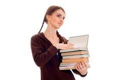La ragazza con i supporti delle trecce lateralmente distoglie lo sguardo e giudica i libri isolati su fondo bianco Fotografie Stock Libere da Diritti