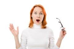La ragazza con i vetri da portare dei capelli rossi è stata sorpresa fotografie stock libere da diritti