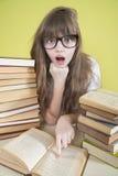La ragazza con i vetri ha letto il libro qualcosa che stupisce Immagini Stock