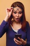 La ragazza con i vetri ottiene gli sms Fotografie Stock