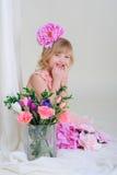 La ragazza con il blesyatschimi piacevole dei denti osserva il fiore nei suoi capelli ed a Fotografia Stock