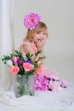 La ragazza con il blesyatschimi piacevole dei denti osserva il fiore nei suoi capelli ed a Immagini Stock