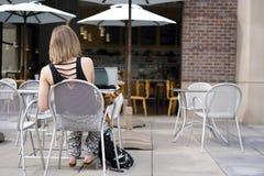 La ragazza con il cane sta sedendosi alla tavola in caffè immagine stock