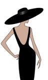 La ragazza con il cappello in vestito nero indietro osserva Fotografia Stock