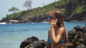 La ragazza con il cellulare si siede sulla roccia ed esamina il mare Bali, Indonesia fotografie stock