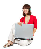 La ragazza con il computer portatile ascolta la musica Fotografie Stock Libere da Diritti