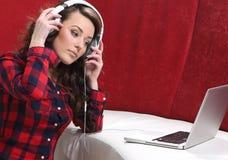 La ragazza con il computer portatile ascolta musica Fotografia Stock