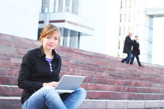 La ragazza con il computer portatile, si siede su una scaletta Immagini Stock