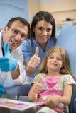 La ragazza con il dentista e la sua manifestazione di aiuto sfogliano su e smil Fotografie Stock Libere da Diritti