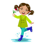 La ragazza con il fiore, bambino in pioggia di Autumn Clothes In Fall Season Enjoyingn e tempo piovoso, spruzza e sguazza Immagini Stock Libere da Diritti