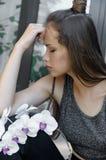 La ragazza con il fiore dell'orchidea è molto triste Fotografia Stock