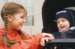 La ragazza con il fratello minore in un carrello Fotografia Stock