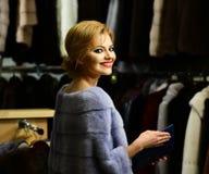 La ragazza con il fronte felice porta il cappotto simile a pelliccia sul fondo dei vestiti immagine stock