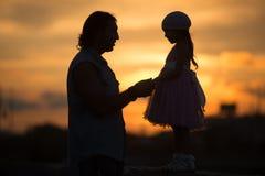 La ragazza con il papà che cammina nella siluetta di tramonto immagine stock libera da diritti