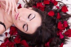 La ragazza con il petalo di rosa dentro sente. Immagine Stock Libera da Diritti