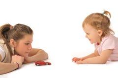La ragazza con il piccolo bambino sta giocando Fotografia Stock